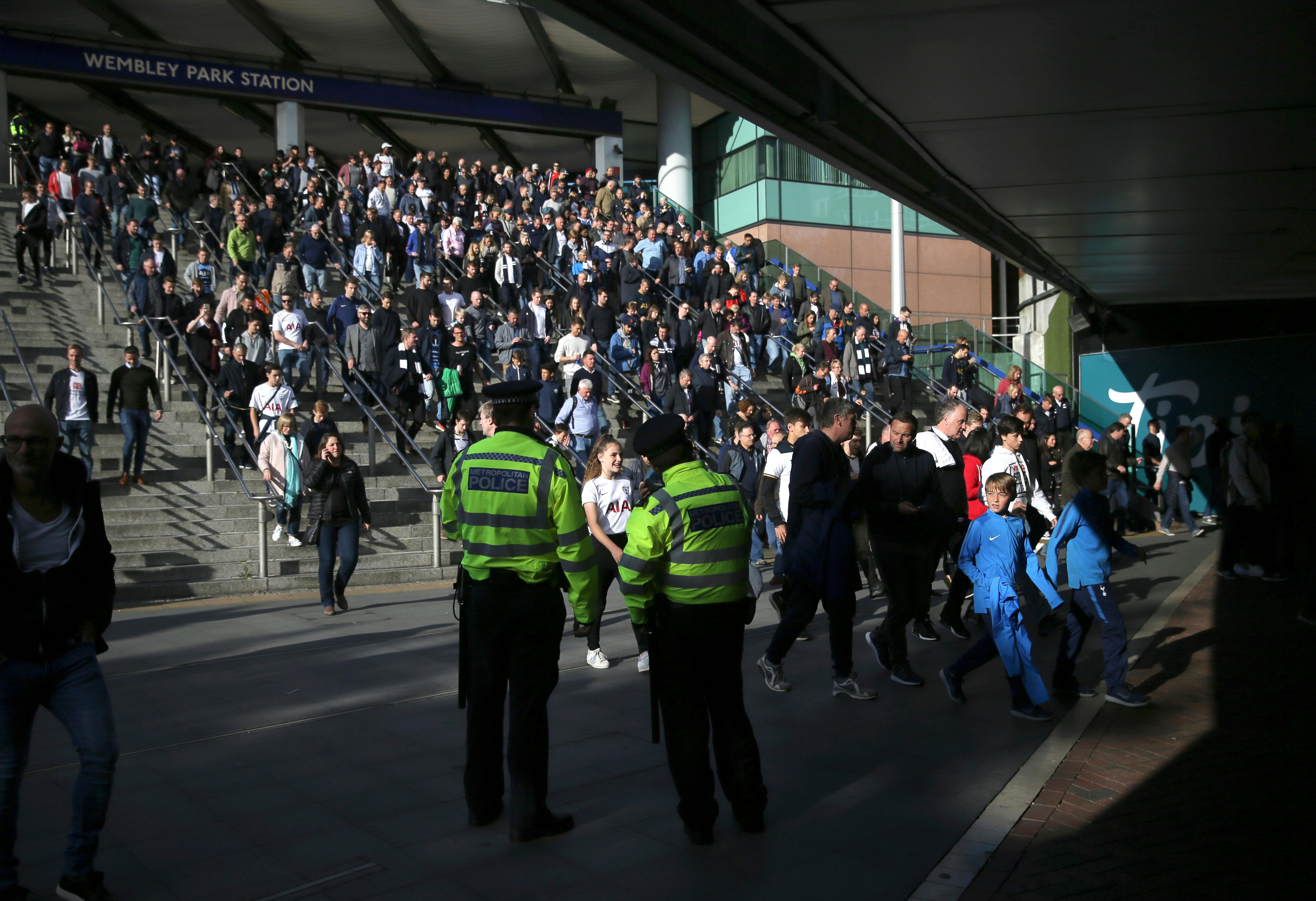 Police observe the crowds outside Wembley Park Station ahead of a soccer match, following a terrorist attack Friday on a train at Parsons Green Station, in London, Saturday Sept. 16, 2017.  A bucket wrapped in an insulated bag caught fire on a packed London subway train Friday, sending commuters running for safety at the height of the morning rush hour. (AP Photo/Tim Ireland)