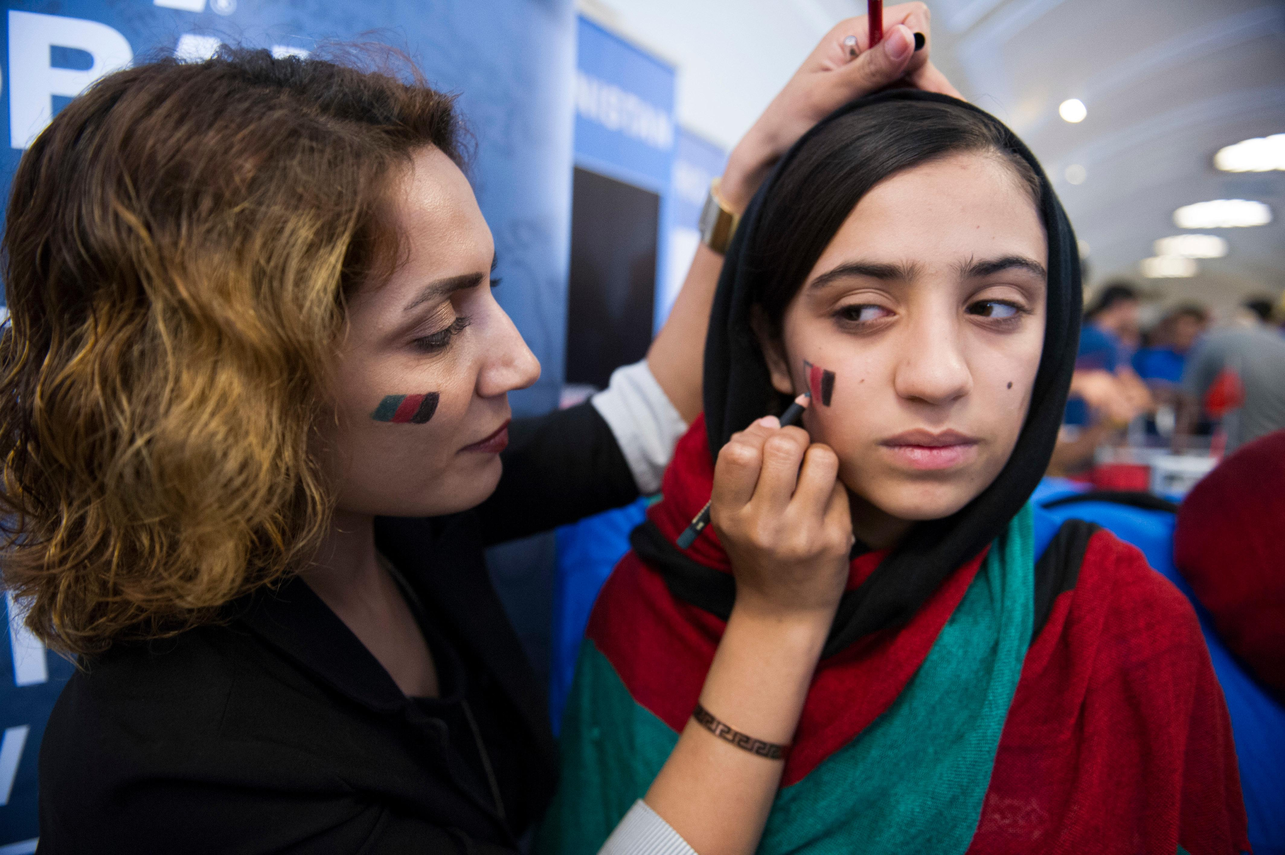 Afghanistan team member Somaya Faryuqi, right, has the flag of Afghanistan drawn on her cheek prior to the opening ceremony for the FIRST Global Challenge 2017, in Washington, Sunday, July 16, 2017. They will be competing against entrants from more than 150 countries in the FIRST Global Challenge. It's the first annual robotics competition designed to encourage youths to pursue careers in math and science.  (AP Photo/Cliff Owen)
