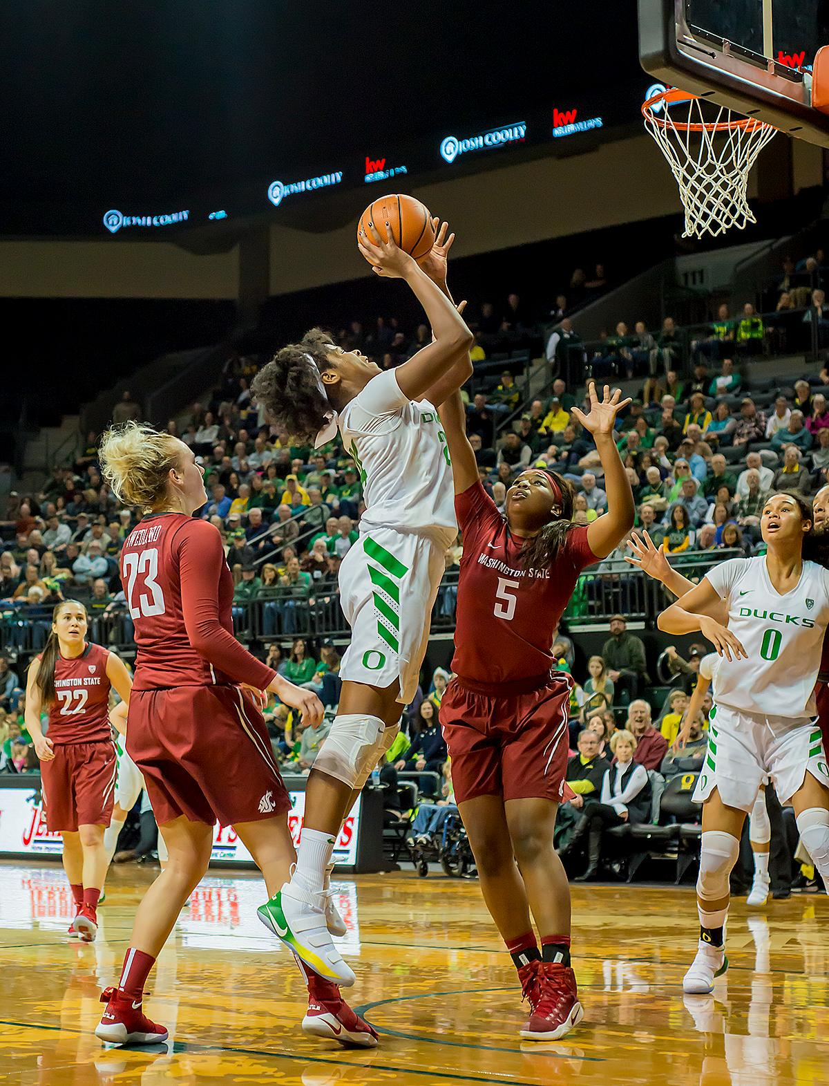 Oregon Ducks Ruthy Hebard (#24) goes up and over Washington State University Cougars Kayla Washington (#5). In their first conference basketball game of the season, the Oregon Women Ducks defeated the Washington State Cougars 89-56 in Matt Knight Arena Saturday afternoon. Oregon's Ruthy Hebard ran up 25 points with 10 rebounds. Sabrina Ionescu shot 25 points with five three-pointers and three rebounds. Lexi Bando added 18 points, with four three-pointers and pulled down three rebounds. Satou Sabally ended the game with 14 points with one three-pointer and two rebounds. The Ducks are now 12-2 overall with 1-0 in conference and the Cougars stand at 7-6 overall and 0-1 in conference play. The Oregon Women Ducks next play the University of Washington Huskies at 1:00 pm on Sunday. Photo by Karly DeWees, Oregon News Lab