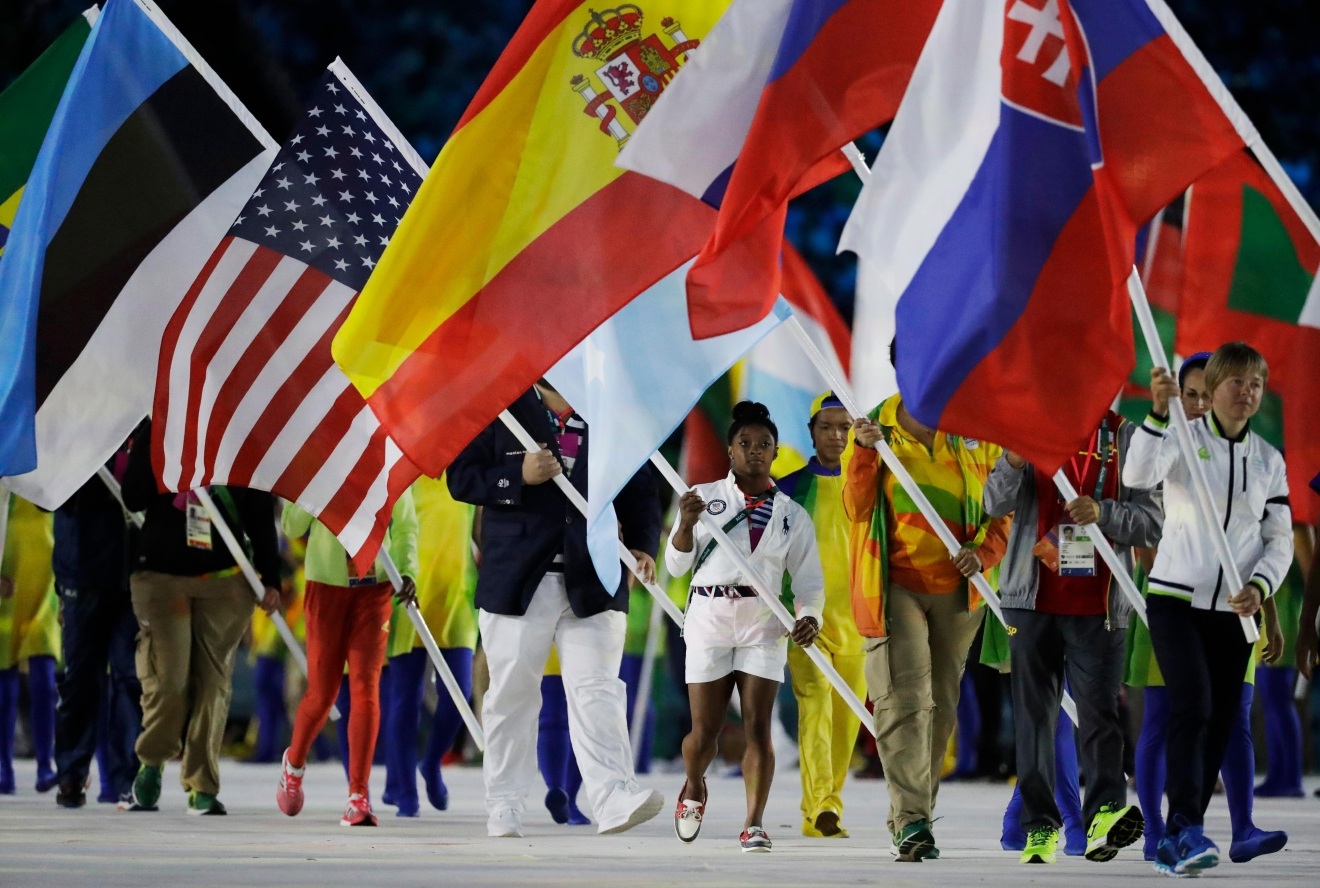 Simone Biles carries the flag of the United States during the closing ceremony in the Maracana stadium at the 2016 Summer Olympics in Rio de Janeiro, Brazil, Sunday, Aug. 21, 2016. (AP Photo/Matt Dunham)