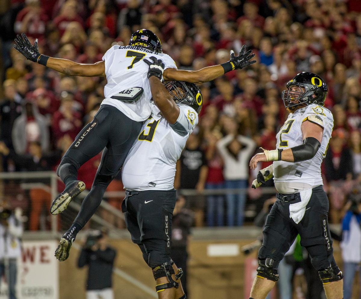 Oregon Ducks Darren Carrington (#7), Tyrell Crosby (#73), and Ivan Faulhaber (#52) celebrate Carrington's touchdown. The Oregon Ducks defeated the Stanford Cardinal 38-36 in Palo Alto, CA at Stanford Stadium Saturday evening after a missed two-point conversion by Stanford. The Ducks win gives them a 7-3 record and a potential to clinch the Pac-12 North divisional title as they prepare for next week's game against USC in Eugene. Katie Pietzold, Oregon News Lab