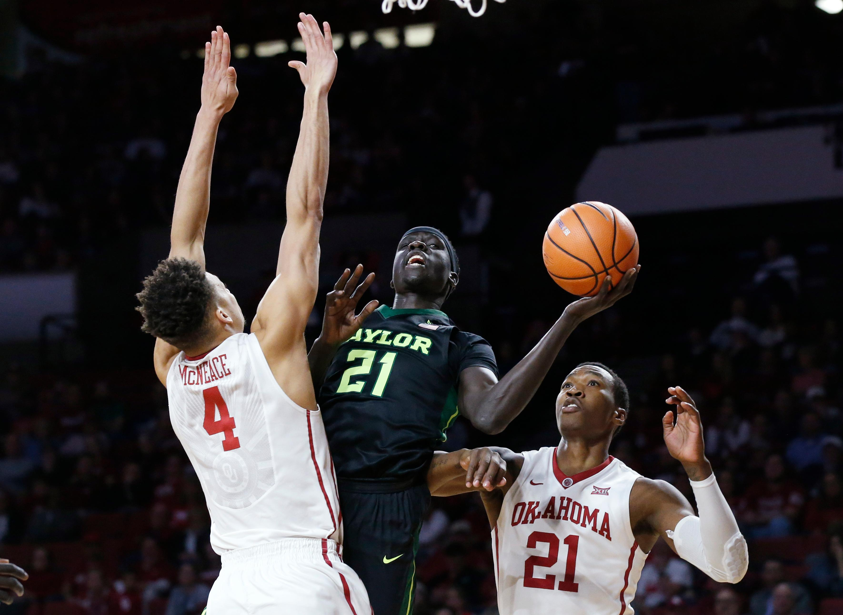 Baylor forward Nuni Omot (21) drives to the basket between Oklahoma center Jamuni McNeace (4) and forward Kristian Doolittle (21) during the first half of an NCAA college basketball game in Norman, Okla., Tuesday, Jan. 30, 2018. (AP Photo/Sue Ogrocki)