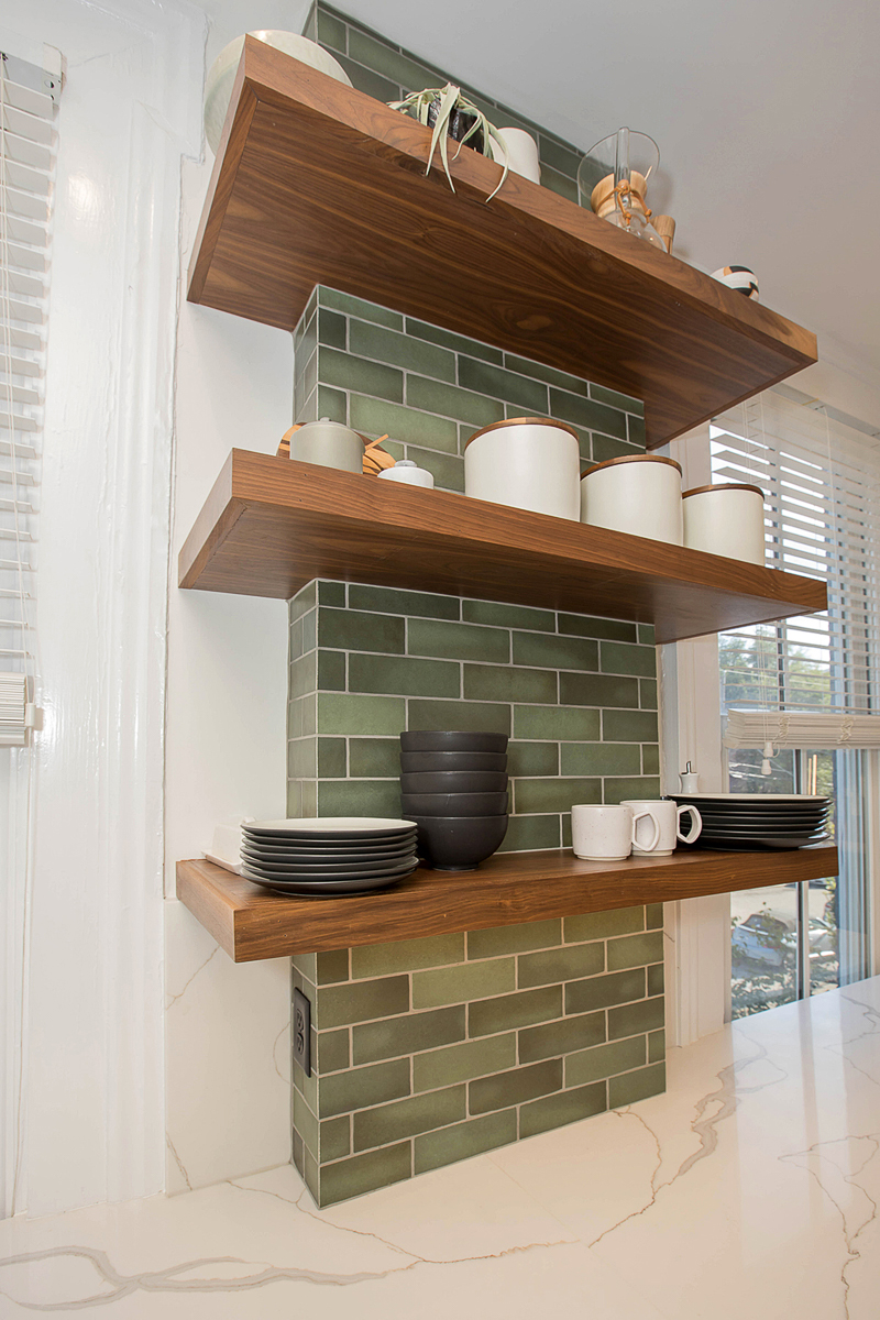 Electrical lines had to be run between windows, so green tile and floating shelves were incorporated to disguise the bump out. / Image courtesy of Neal's Design Remodel // Published: 11.1.20