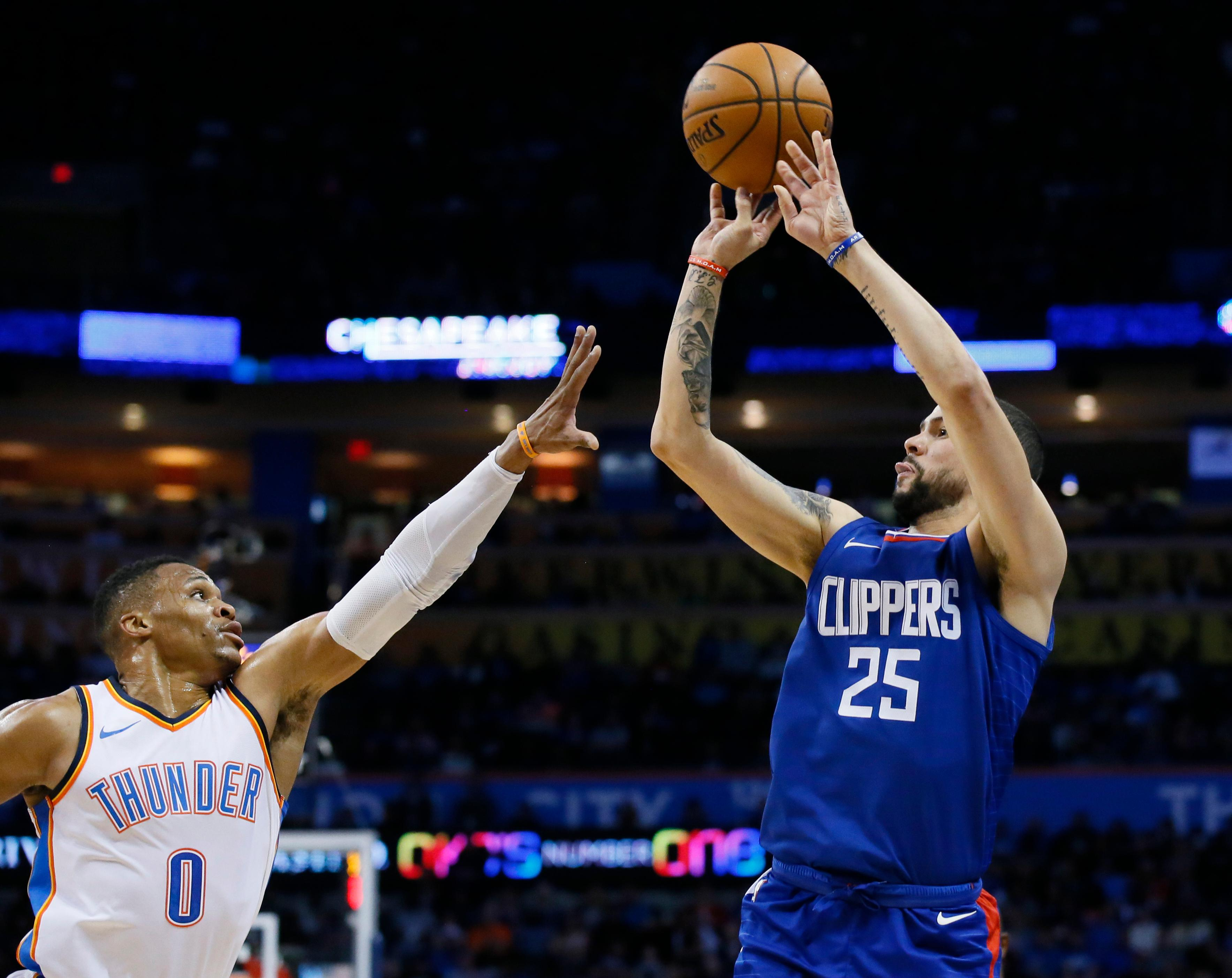 Los Angeles Clippers guard Austin Rivers (25) shoots as Oklahoma City Thunder guard Russell Westbrook (0) defends in the first quarter of an NBA basketball game against the Los Angeles Clippers in Oklahoma City, Friday, Nov. 10, 2017. (AP Photo/Sue Ogrocki)