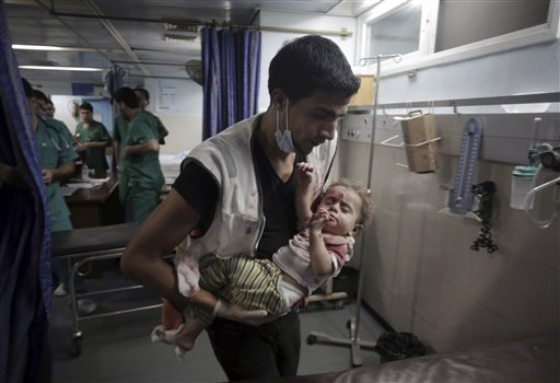 A Palestinian medic carries a wounded girl in the emergency room of Shifa hospital in Gaza City.
