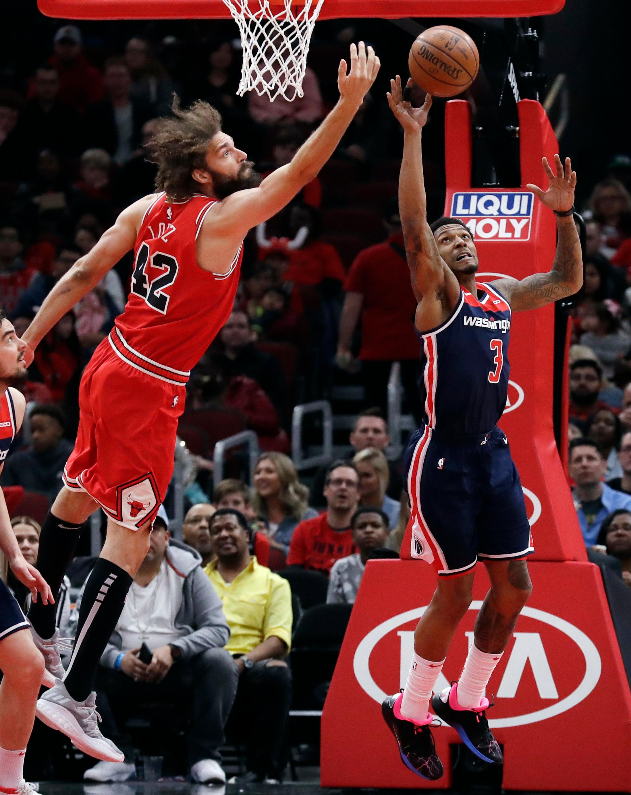 Washington Wizards guard Bradley Beal, right, and Chicago Bulls center Robin Lopez reach for a rebound during the first half of an NBA basketball game Wednesday, March 20, 2019, in Chicago. (AP Photo/Nam Y. Huh)