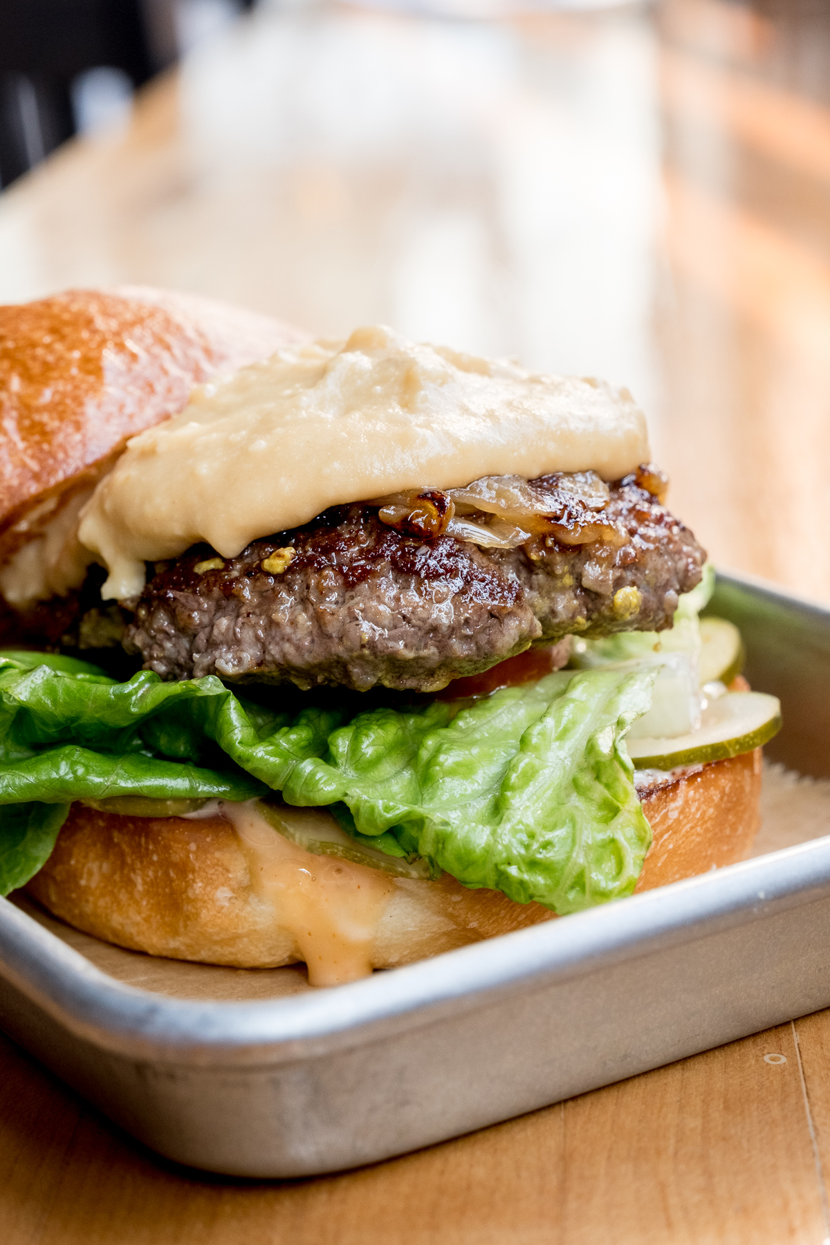 Grass-fed beef cheeseburger with caramelized onions and house-made beer cheese / Image: Daniel Smyth Photography